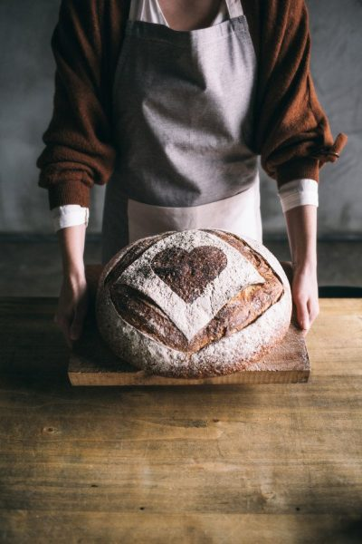 Bakery employee holding a freshly baked loaf of bread.